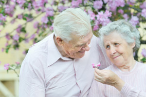 Two seniors with one holding a flower